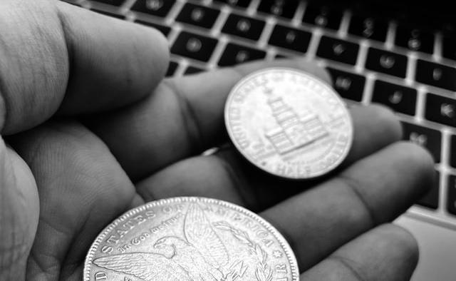 Cost of website, coins held over laptop